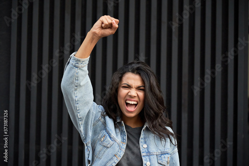 Fotografija Angry brave African young woman standing on black background raising fist and screaming