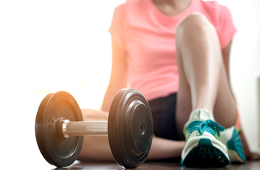Woman exercise by personal trainer at gym and then be tired. She sit on floor for rest that dumbbell in front of her. Women wearing sport shoes.