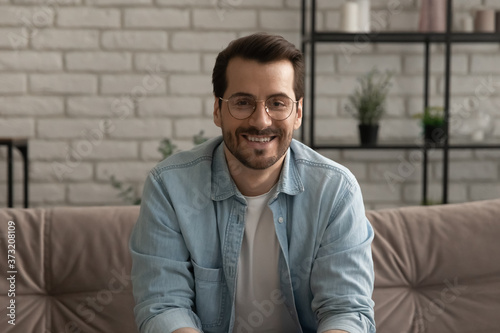 Portrait of happy young Caucasian man in glasses sit on sofa in living room at h Billede på lærred