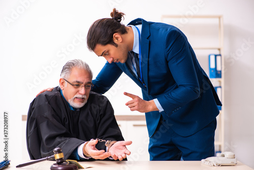 Police inspector arresting old judge in court Canvas Print
