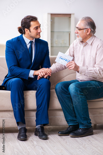 Young male lawyer visiting old man in testament concept Canvas Print