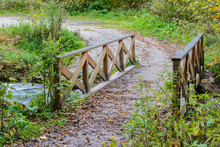 Wooden Bridge In The Forest Covered With Autumn Foliage. Autumn Landscape Near The Blue Lake.