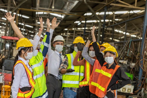 Fototapeta Team of mechanic engineers with face mask celebrate a great success during COVID-19 outbreak