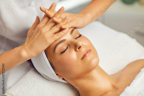 Cosmetologist making facial massage or treatment for young womans face in beauty Fototapet