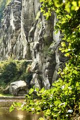 Obraz na Szkle Góry Selective focus vertical shot of a rock formation near a river