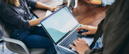 Foto Mockup image of a woman using laptop with blank screen on wooden table