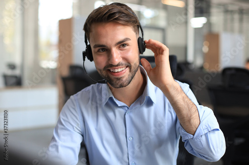 Papel de parede Smiling friendly handsome young male call centre operator.