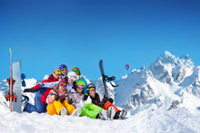 Large Group Of Happy Young Adults Lay In Snow Wave Hands With Snowboards And Ski Over Mountain Peaks