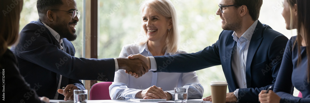 Fototapeta Banner image. African and caucasian millennial businessmen colleagues shaking hands on meeting in office, diverse enterpreneurs striking good deal, multiethnic teammates succeed in common project work