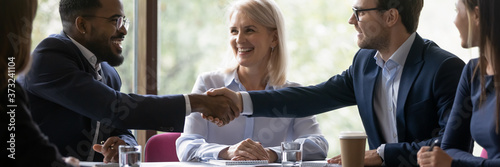 Fototapeta Banner image. African and caucasian millennial businessmen colleagues shaking hands on meeting in office, diverse enterpreneurs striking good deal, multiethnic teammates succeed in common project work obraz