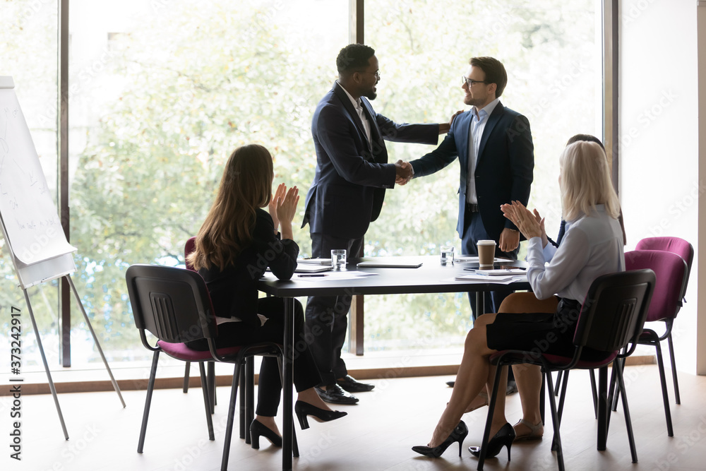 Fototapeta Black chief ceo shaking hand of millenial european worker manager welcoming or thanking for good job while staff applaude, happy young businessman is awarded by boss in presence of colleagues