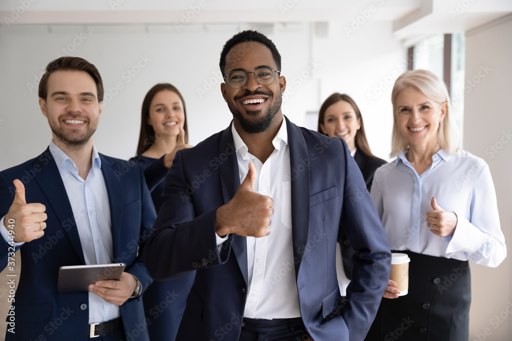 Fototapeta Portrait of smiling successful black african ceo, boss or team leader with happy friendly diverse colleagues subordinates staff group of different age and race looking at camera and showing thumbs up