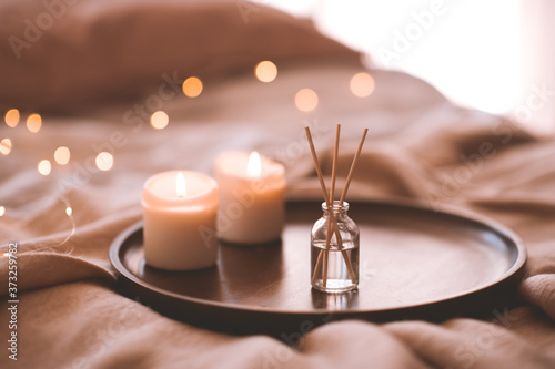 Fototapeta Aroma bamboo sticks in bottle with scented liquid with candles staying on wooden tray in bed closeup. obraz
