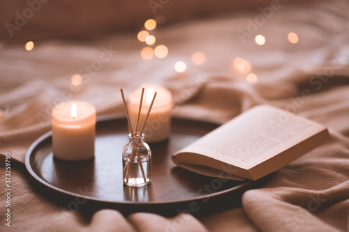 Fotografie, Obraz Bamboo sticks in bottle with scented candlrs and open book on wooden tray in bed closeup