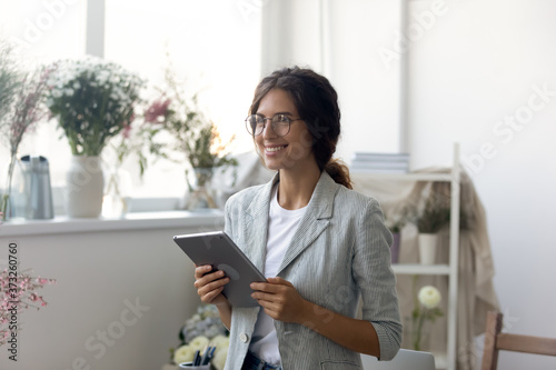 Happy young dreamy woman holding computer tablet in hands, looking away, thinking of future challenges, planning meeting with clients or personal brand development online, inspiration concept.