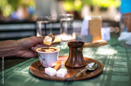 Fototapeta Traditional turkish black coffee and sweet lokum dessert on a table in a restaurant