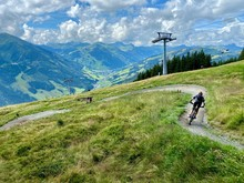 Unrecognicable Bikers On A Mountainbike Trail In Saalbach In The Austrian Alps In Summer With Dramatic Sky And Cable Car In The Background.