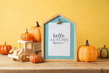 Hello Autumn Concept With Pictute Frame, Toy Truck And Pumpkin Decor On Wooden Table Over Yellow Background. Fall Season Greeting Card.