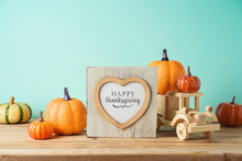 Happy Thanksgiving Concept With Photo Frame, Toy Truck And Pumpkin Decor On Wooden Table Over Blue Background. Autumn Season Greeting Card.