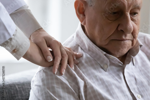 Close up compassionate young female doctor holding hands on shoulders of depressed old retired patient Fototapeta