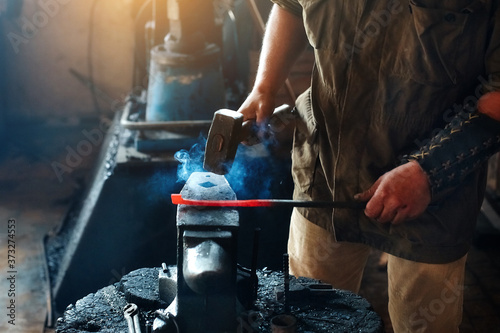 Canvastavla Blacksmith working metal with hammer on the anvil in the forge