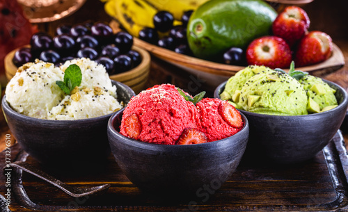 Obraz na plátně vegan ice cream made with organic fruits, with tropical fruits in the background