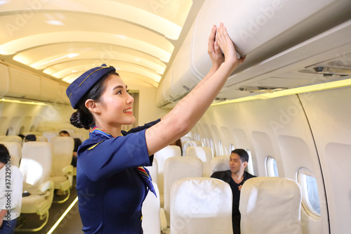 Fotografía Female flight attendant closing the overhead luggage compartment lid after all p