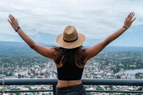 Fototapeta Mujer joven con los brazos abiertos observando una ciudad.
