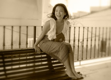 Lifestyle Portrait Of Young Attractive And Beautiful Asian Korean Woman Sitting Outdoors At City Park Bench Happy And Relaxed Touring Seville Town In Spain During Holidays Travel In Europe