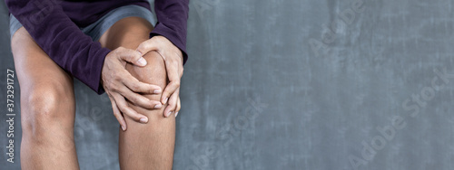 Photo Young woman knee pain on concrete wall for texture background with copy space