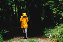 Woman In Yellow Raincoat Walking By Rainy Forest