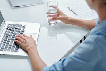 Hands of contemporary businesswoman in blue shirt having glass of water by desk