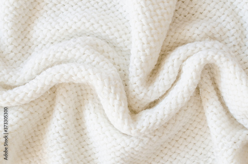 Beige knitted woolen background. Knitwear fabric texture. Fotobehang