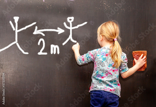 Fotografia Little girl writing concept of social distancing on black chalkboard