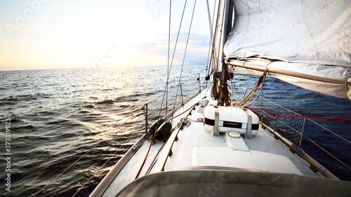White sail yacht tilted in a wind at sunset Billede på lærred
