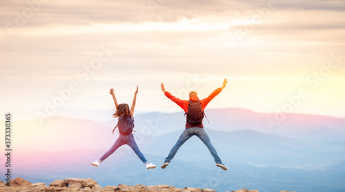 Two happy tourists man and woman friends couple jump on top of mountain, back vi фототапет
