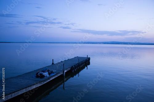 Fotografía novios tumbados y abrazados en un embarcadero de la albufera (valencia) mientras