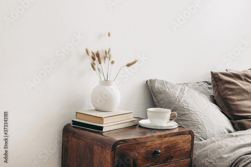 Modern white ceramic vase with dry Lagurus ovatus grass and cup of coffee on retro wooden bedside table Fototapete