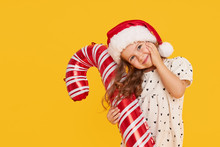 A Cute Little Girl Child In A Smart Dress And A Santa Hat Holds An Inflatable Shape Of A Candy Cane On A Yellow Background. 2021 New Year Holidays Concept And Childrens New Year Gifts Advertising