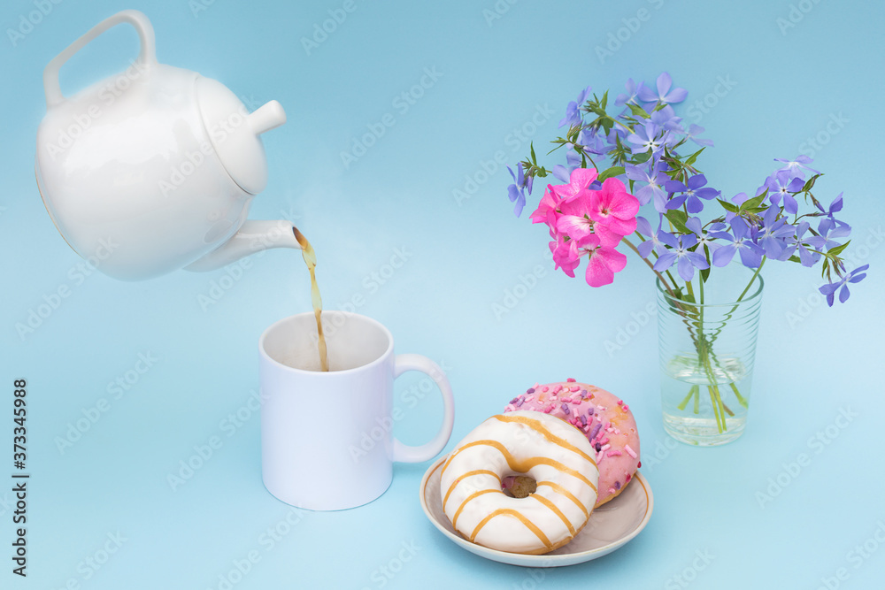 Fototapeta A hot drink is poured into a white mug from a white teapot without logos. On the table are two fragrant donuts and a bouquet of blue and bright pink flowers. Photo in pastel colors, without people.