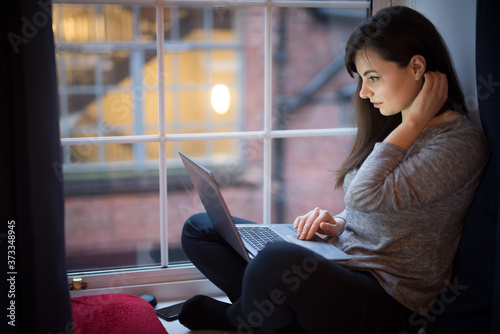 Obraz na plátně A woman types on her laptop and fixes her hair while sitting by the window in th
