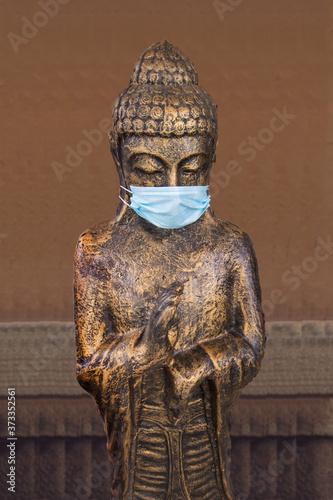 Buddha figure with surgical mask Fototapeta