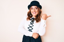 Young Beautiful Caucasian Woman Wearing Elegant Style And Hat Pointing Thumb Up To The Side Smiling Happy With Open Mouth