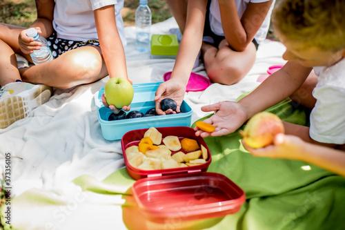 School children in white t shirt eating lunch during their lunch break at school Fototapet