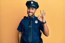 Handsome Hispanic Man Wearing Police Uniform Smiling Positive Doing Ok Sign With Hand And Fingers. Successful Expression.