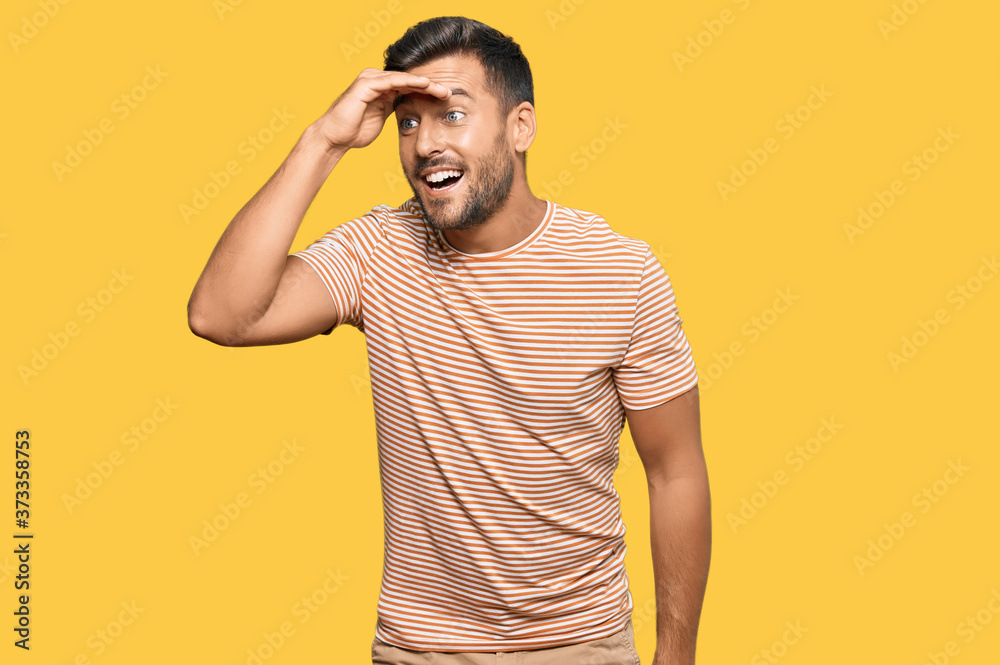 Fototapeta Handsome hispanic man wearing casual clothes very happy and smiling looking far away with hand over head. searching concept.