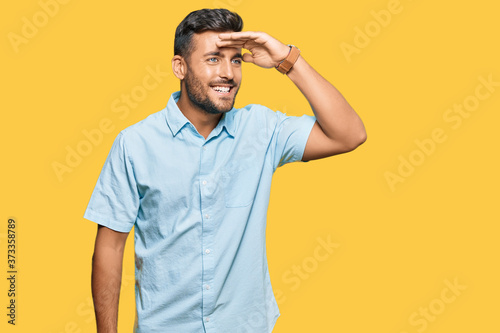 Stampa su Tela Handsome hispanic man wearing casual clothes very happy and smiling looking far away with hand over head