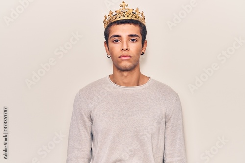 Obraz na plátně Young african amercian man wearing prince crown with serious expression on face