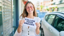 Young Caucasian Woman Smiling Happy Holding Follow Your Dreams Message Paper At The City