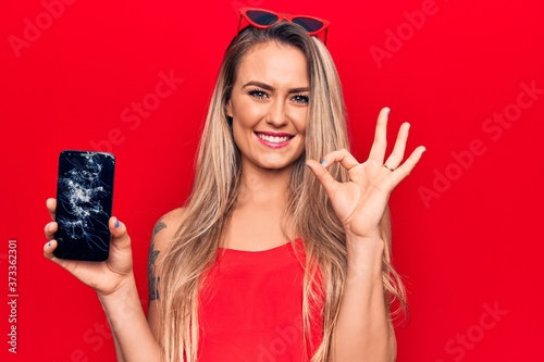 Leinwand Poster Young beautiful blonde woman holding broken smartphone showing cracked screen do